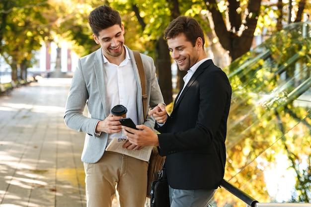 Photo de beaux hommes d'affaires en costume à l'aide de smartphone tout en marchant en plein air à travers le parc verdoyant avec du café à emporter, pendant la journée ensoleillée
