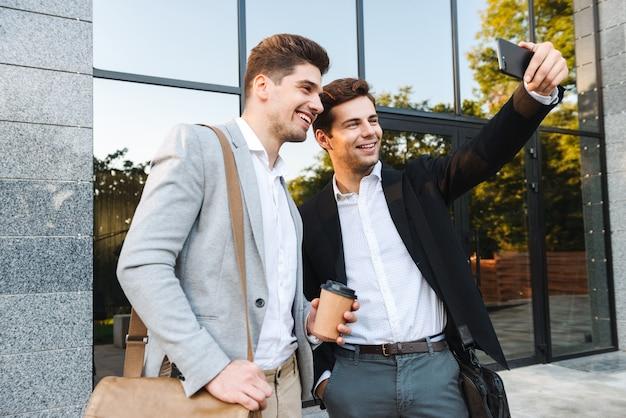 Photo de beaux hommes d'affaires en costume à l'aide de smartphones pour selfie, debout à l'extérieur près du bâtiment avec café à emporter
