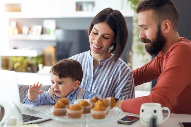 Photo de beaux jeunes parents avec leur bébé regardant des dessins animés sur un ordinateur portable à la maison.