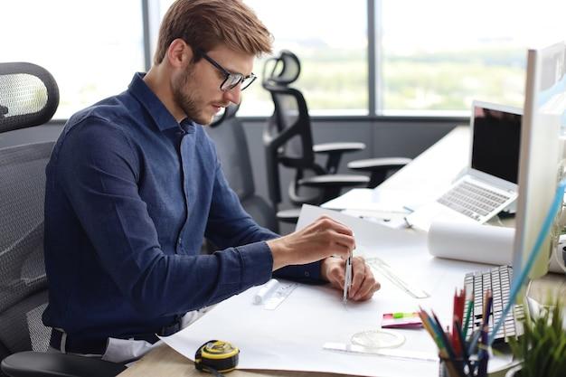 Photo d'un bel architecte masculin travaillant sur un dessin dans son bureau.