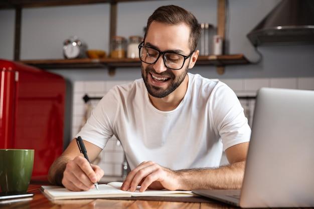 Photo de bel homme 30 ans portant des lunettes d'écrire des notes tout en utilisant un ordinateur portable argenté sur la table de cuisine