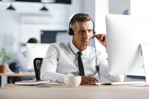 Photo de bel homme de 30 ans portant des vêtements de bureau et des écouteurs, assis par ordinateur dans le centre d'appels