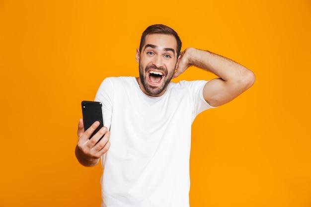Photo de bel homme 30 s en tenue décontractée tenant le smartphone, isolé