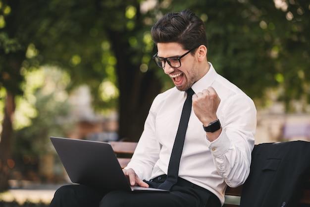 Photo de bel homme d'affaires en costume assis sur un banc dans un parc verdoyant et travaillant sur ordinateur portable pendant la journée ensoleillée