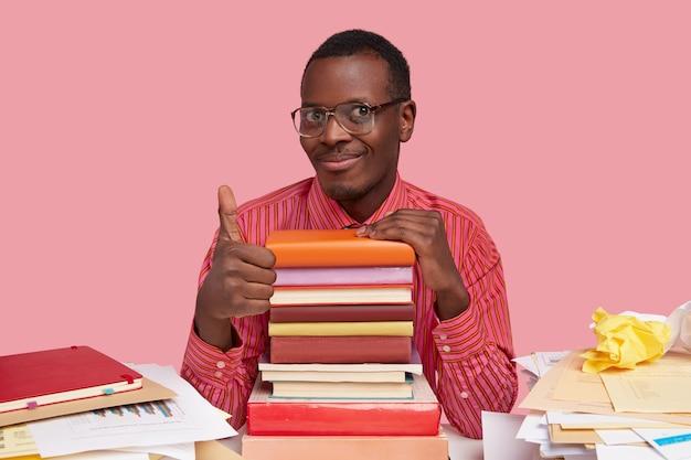 Photo de bel homme afro-américain fait un geste correct, montre son approbation, a un sourire doux