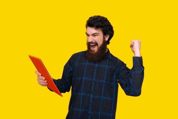 Photo d'un bel homme à la barbe crie et célèbre avec le bras levé, tout en tenant une tablette, sur le mur jaune
