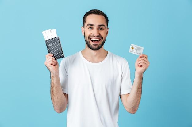 Photo d'un bel homme brune portant un t-shirt basique souriant tout en tenant des billets de voyage avec passeport et carte de crédit isolés sur bleu