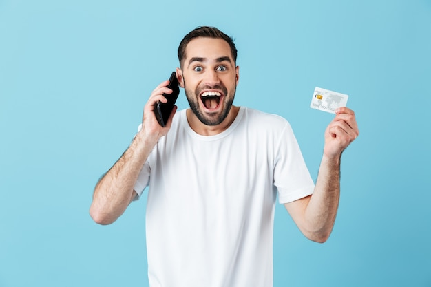 Photo d'un bel homme brune portant un t-shirt basique souriant tout en tenant un smartphone et une carte de crédit isolés sur bleu