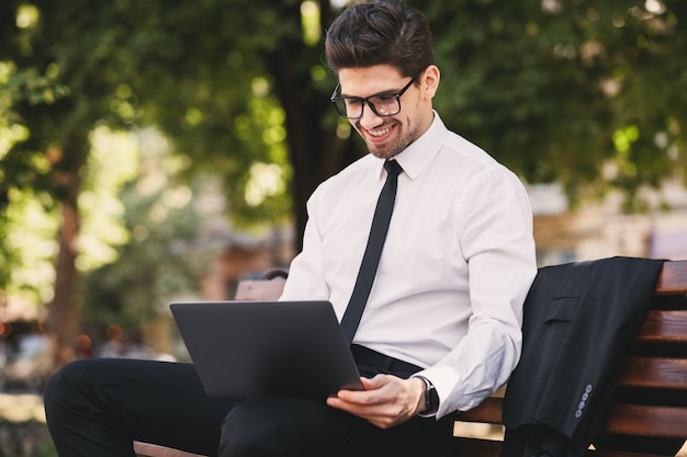 Photo de bel homme en costume professionnel assis sur un banc dans un parc verdoyant et travaillant sur un ordinateur portable pendant la journée ensoleillée