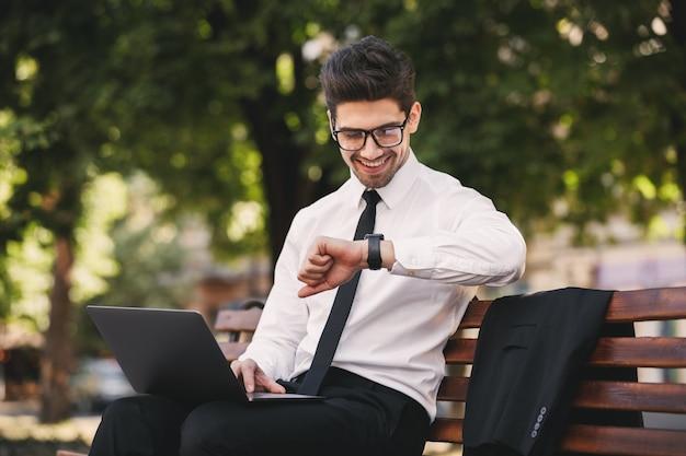 Photo de bel homme en costume professionnel travaillant sur un ordinateur portable dans un parc verdoyant et regardant une montre-bracelet
