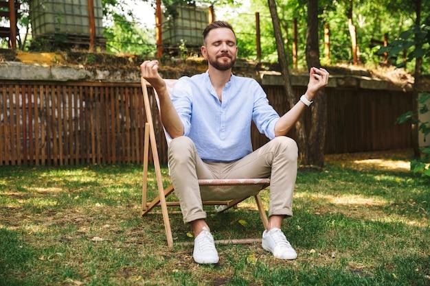 Photo de bel homme détendu assis dans une chaise longue avec les yeux fermés et le geste d'yoga, pendant le repos dans le parc verdoyant