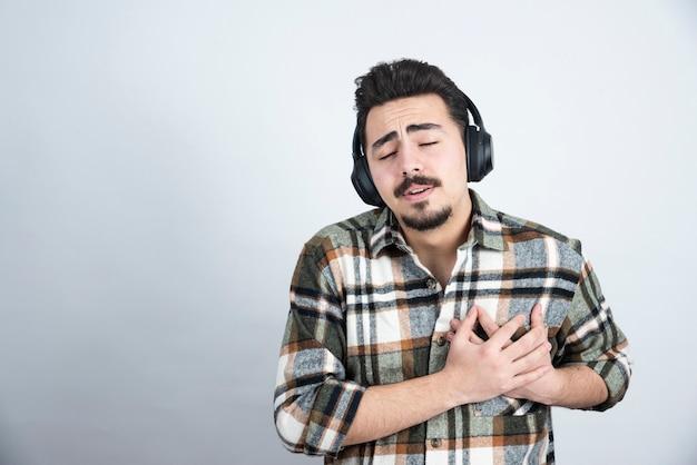 Photo de bel homme avec des écouteurs se tenant sur un mur blanc.