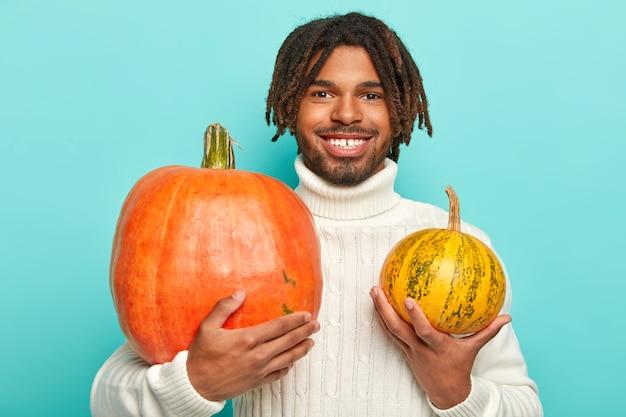 Photo de bel homme hipster joyeux avec des dreadlocks, sourire à pleines dents, détient deux citrouilles de taille différente, porte un pull blanc chaud, isolé sur un mur bleu