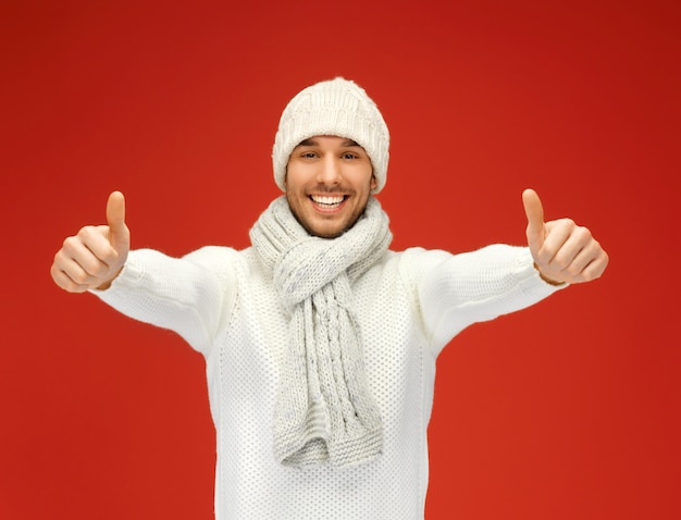 Photo d'un bel homme en pull chaud, bonnet et écharpe.