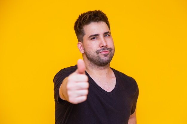 Photo d'un bel homme en t-shirt décontracté souriant à la caméra avec le pouce vers le haut.