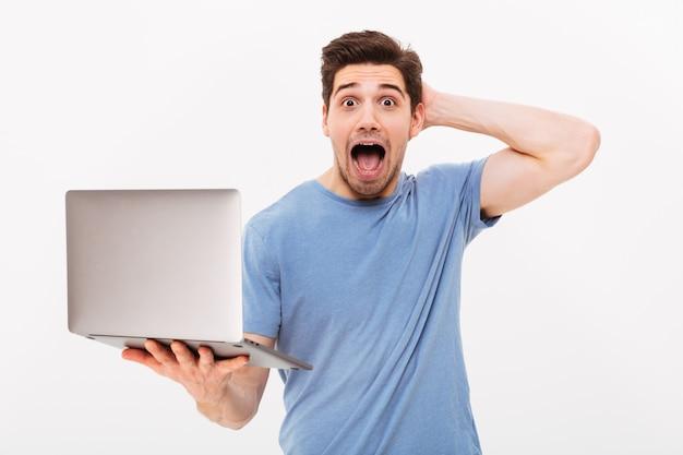 Photo de bel homme en t-shirt décontracté tenant un ordinateur portable argenté et regardant la caméra avec excitation ou choc, isolé sur mur blanc