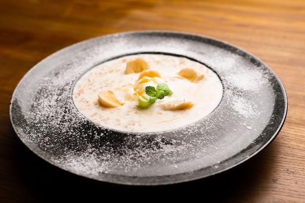 Photo de belle assiette avec flocons d'avoine et banane décorée à la menthe sur table en bois au restaurant