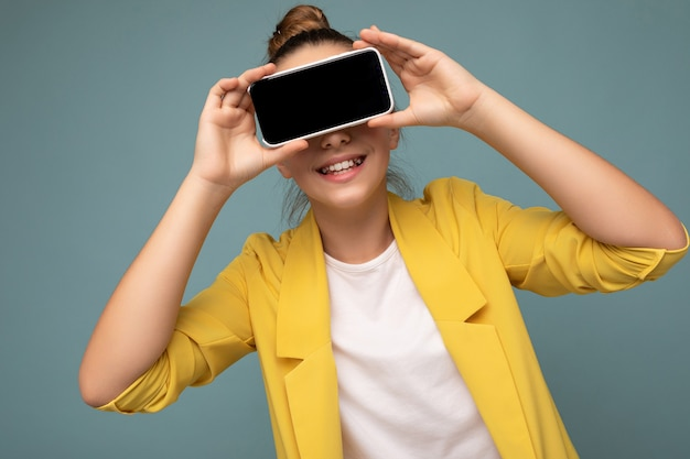 Photo d'une belle dame souriante belle portant une tenue élégante décontractée, debout isolée sur fond avec espace de copie tenant un smartphone montrant le téléphone à la main avec un écran vide pour la maquette