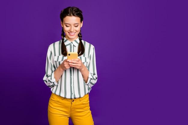 Photo de belle dame tenant téléphone écrit nouveau post instagram bonne humeur positive porter chemise rayée pantalon jaune isolé fond de couleur pourpre
