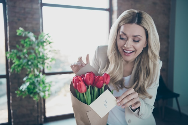 Photo de belle femme d'affaires à la petite carte postale bouquet de tulipes fraîches