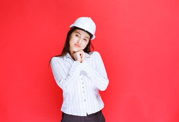 Photo d'une belle femme d'affaires portant un chapeau de sécurité debout contre le mur rouge.