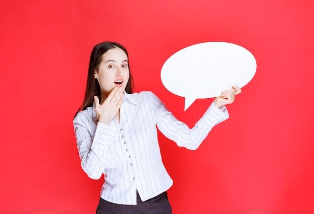 Photo d'une belle femme d'affaires tenant une bulle de dialogue vide.