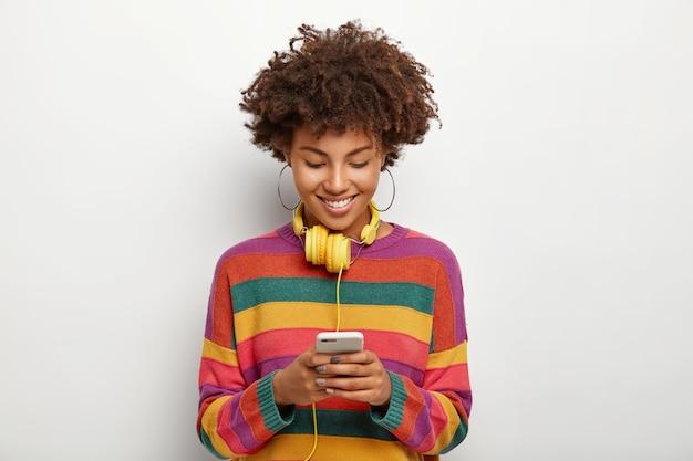 Photo d'une belle femme afro-américaine concentrée dans un smartphone, aime bavarder en ligne, télécharge de la musique sur une liste de lecture pour l'écouter dans un casque, a les cheveux noirs bouclés, porte une tenue décontractée