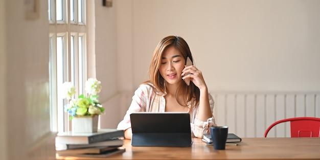 Photo d'une belle femme à l'aide d'un smartphone pour appeler quelqu'un tout en étant assis devant une tablette informatique avec étui à clavier à une table de travail en bois sur un salon confortable
