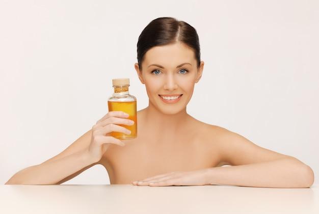 Photo de belle femme avec une bouteille d'huile