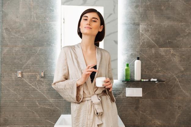 Photo de belle femme brune debout près d'un miroir et prendre soin de la peau, avec de la crème pour le visage à la maison dans la salle de bain