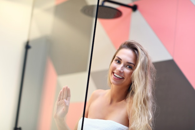 Photo de belle femme caucasienne blonde posant dans la salle de bain avec les cheveux mouillés.
