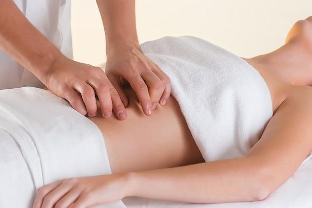 La photo de la belle femme dans le salon de massage et les mains des hommes sur son corps