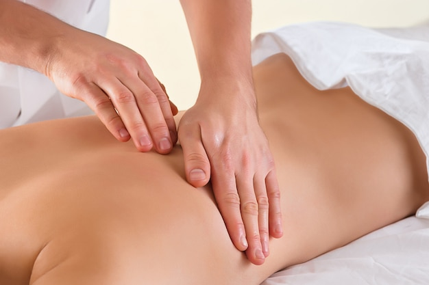 La photo de la belle femme dans le salon de massage et les mains mâles se bouchent