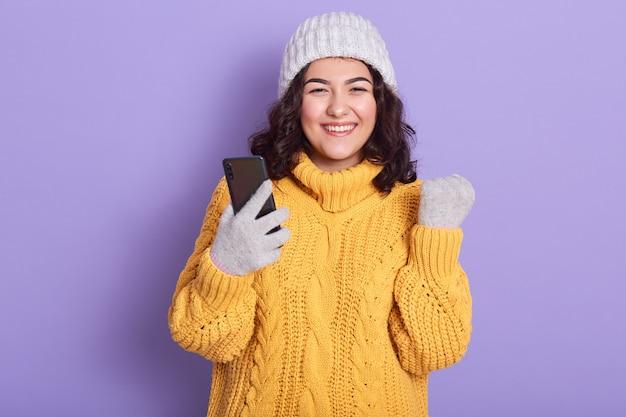 Photo de belle femme énergique aux cheveux bouclés noirs, serrant le poing, tenant le smartphone, souriant sincèrement, ayant une expression faciale agréable, étant de bonne humeur. concept d'appareils modernes.