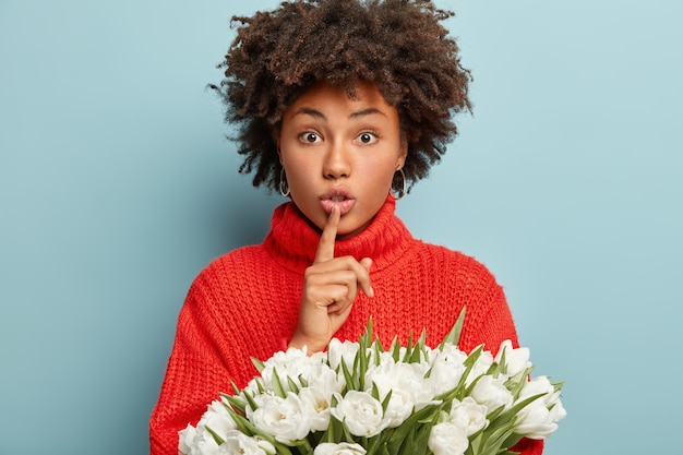 Photo d'une belle femme étonnée fait un geste de silence, garde son index sur les lèvres, porte un pull rouge tricoté, tient des fleurs de printemps blanches, isolées sur un mur bleu. chut signe. ne dis pas de secret