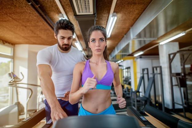 Photo d'une belle femme en forme sur une piste de course dans une salle de sport alors que son entraîneur personnel se tient derrière elle.