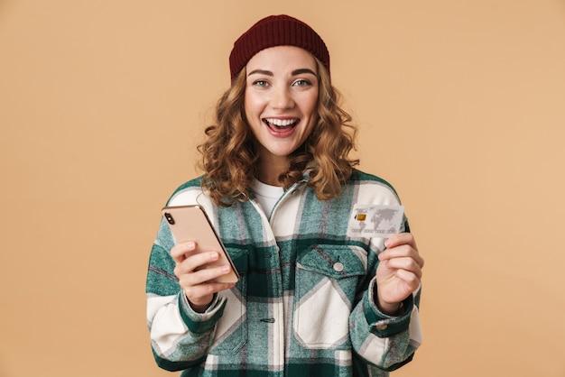 Photo d'une belle femme joyeuse en bonnet tricoté tenant une carte de crédit et un téléphone portable isolé sur beige