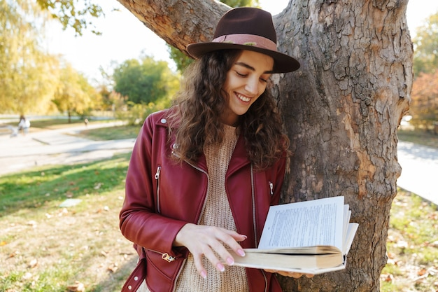 Photo d'une belle femme mignonne debout dans le parc près du livre de lecture d'arbre.
