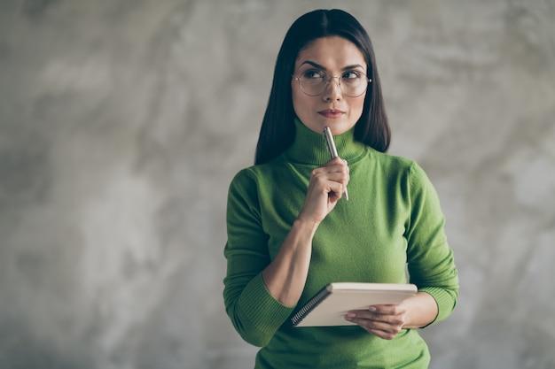 Photo de belle femme pensive touchant le menton avec pan tenant le bloc-notes à la recherche dans un espace vide pour rechercher de nouvelles informations mur gris isolé fond de couleur béton