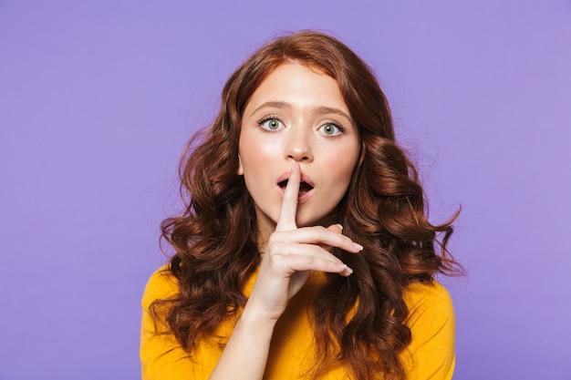 Photo de belle femme rousse portant des vêtements jaunes tenant le doigt sur ses lèvres et demandant à garder le secret sur violet