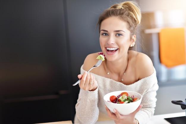Photo de belle femme souriante mangeant une salade végétarienne biologique fraîche dans une cuisine moderne
