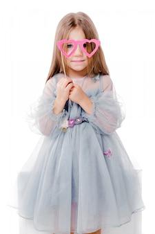 Photo de belle fille dans une robe grise et des lunettes en carton en forme de coeurs