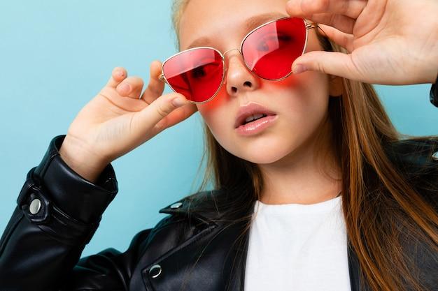 Photo d'une belle fille élégante dans une veste noire et des lunettes rouges sur fond bleu