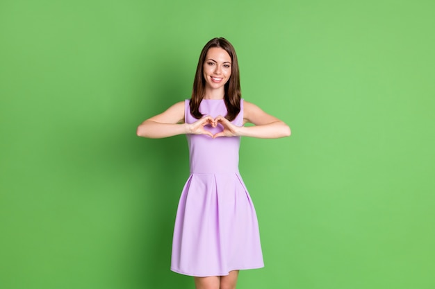 Photo de belle gentille fille dame sourire à pleines dents montrer forme de coeur deux mains regarder caméra démontrer amour sentiments gentillesse habillé vêtements violets isolé fond de couleur vert pastel