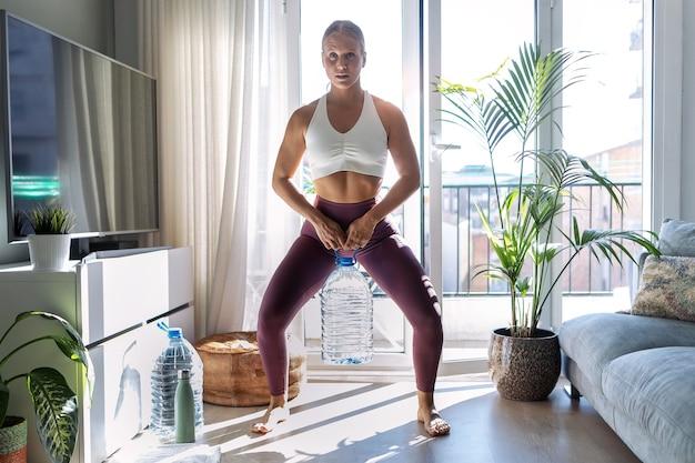 Photo d'une belle gymnaste faisant des exercices en soulevant des bouteilles d'eau de huit litres dans le salon à la maison.