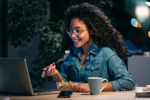 Photo d'une belle jeune femme d'affaires afro travaillant avec un ordinateur tout en mangeant des pâtes assises au bureau.