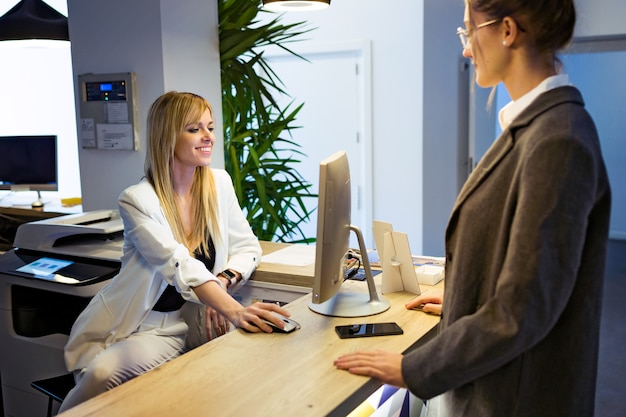 Photo d'une belle jeune femme d'affaires faisant l'enregistrement avec un ordinateur à la réception de l'hôtel.