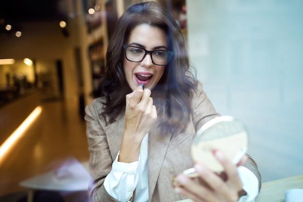Photo d'une belle jeune femme d'affaires regardant dans le miroir et appliquant du rouge à lèvres dans le café.