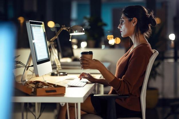 Photo d'une belle jeune femme d'affaires travaillant avec un ordinateur tout en buvant du café assis au bureau.