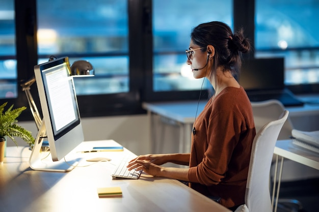 Photo d'une belle jeune femme d'affaires travaillant avec un ordinateur tout en parlant avec des écouteurs assis au bureau.